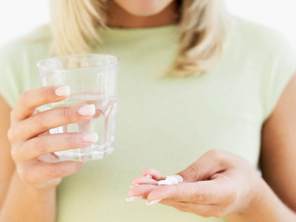 Женщина держит в руках стакан с водой и таблетки