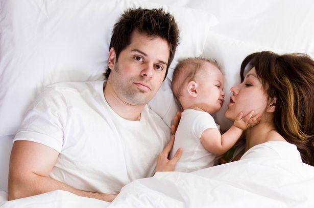 Мужчина, женщина и ребенок между ними в постели