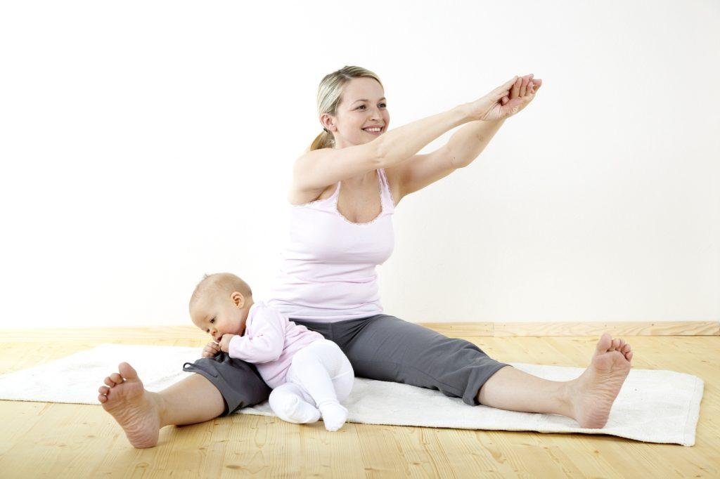Молодая мама занимается спортом, ребенок сидит рядом с ней