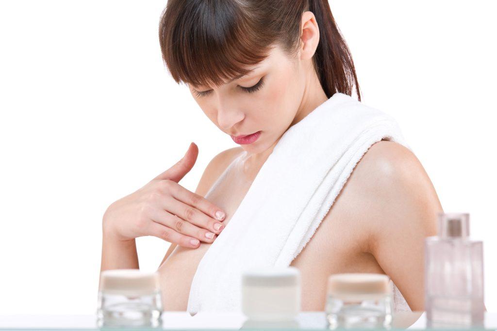 Женщина мажет грудь кремом