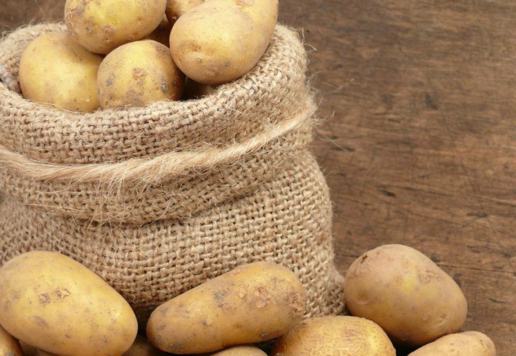 Картошка в мешке на деревянном полу