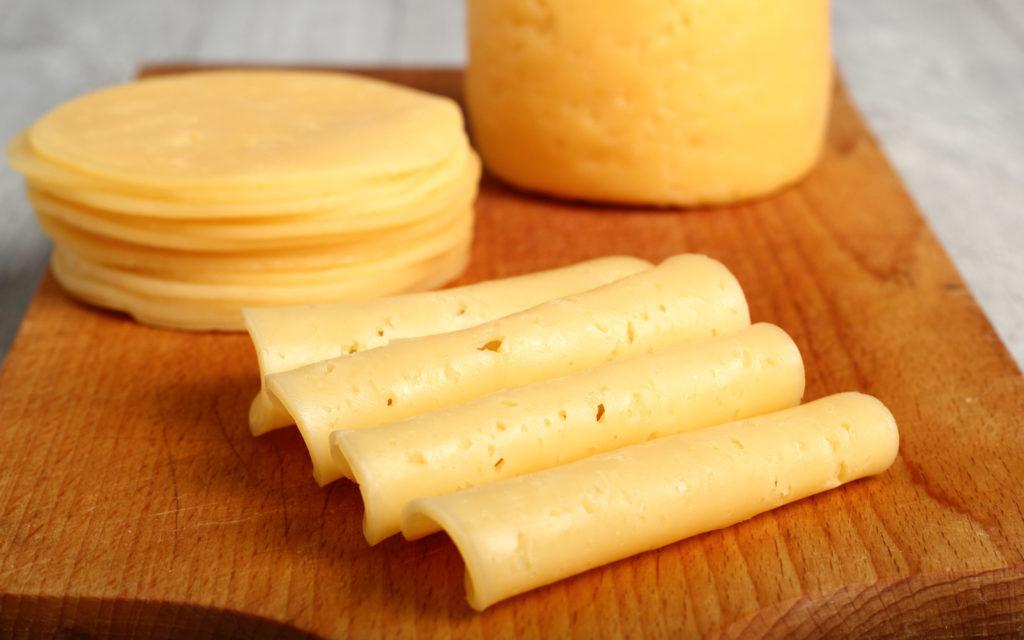 Сыр, нарезанный кусочками, на разделочной доске