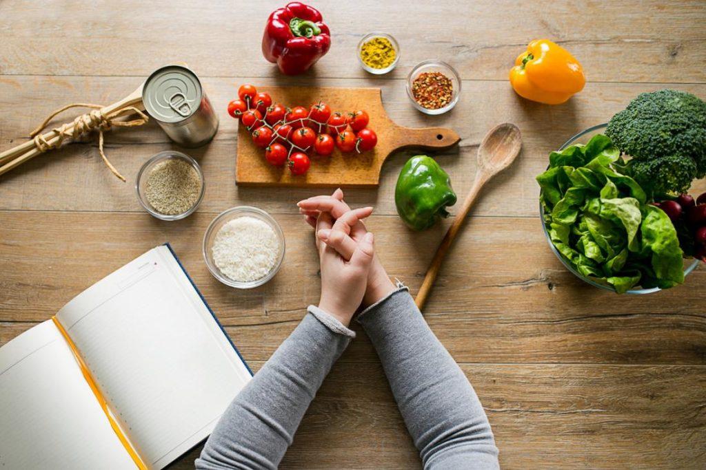 Овощи, крупы, специи, раскрытая тетрадь и сложенные женские руки на деревянном столе