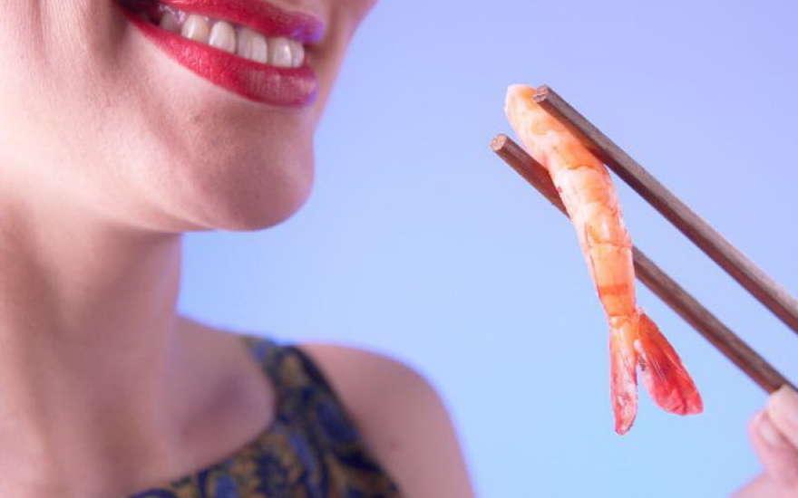 Девушка подносит палочками креветку ко рту