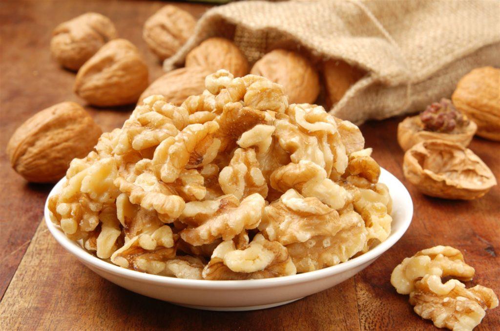 Грецкие орехи чищенные в тарелке на деревянном столе