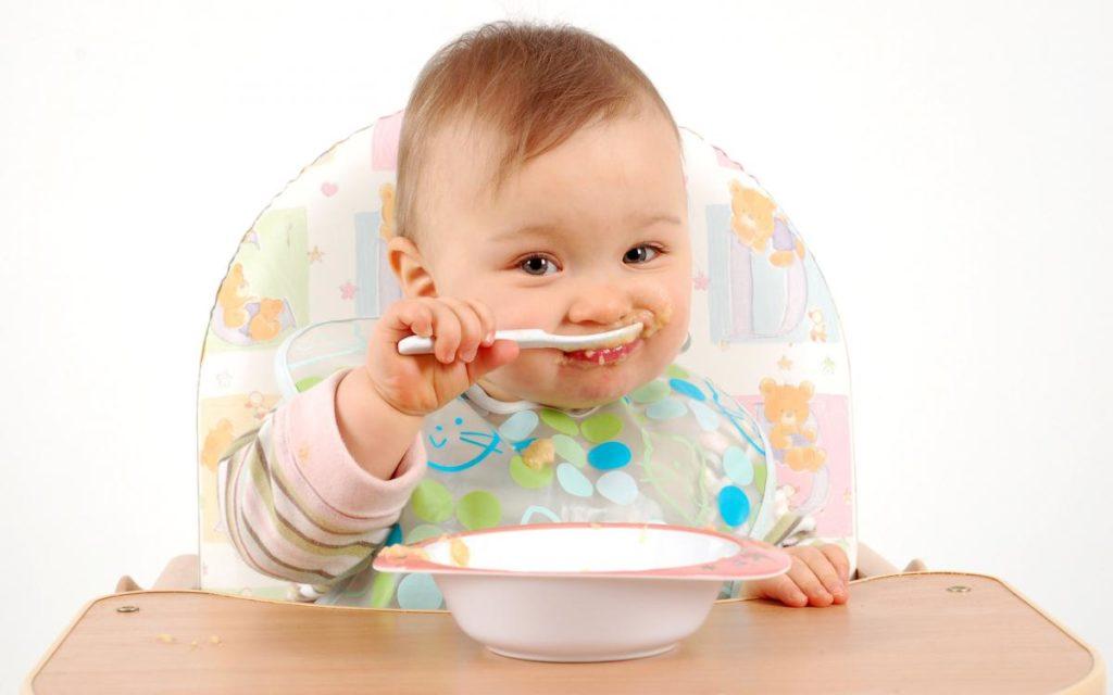 Ребенок сидит за столом и ест ложкой пюре из тарелки