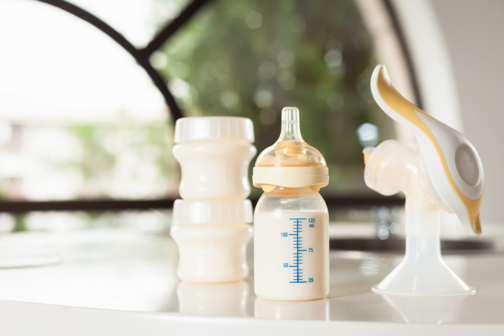 Детская бутылочка с молоком и молокоотсос на столе