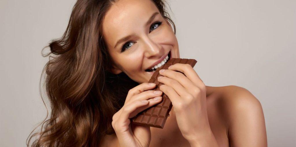 Девушка надкусывает плитку шоколада