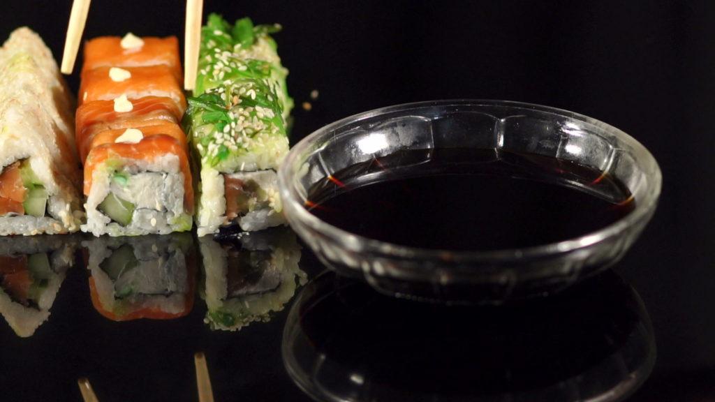Соевый соус в пиале и суши с палочками на заднем плане на черном фоне