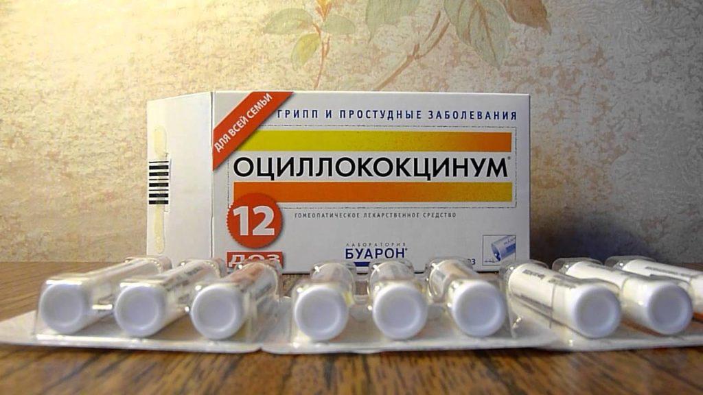 Упаковка Оциллококцинум и баночки с гранцлами на столе на фоне светлых обоев