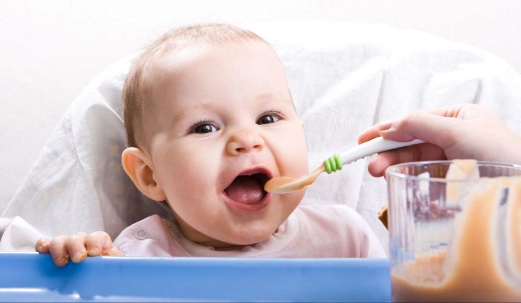 Ребенок открывает рот перед ложкой