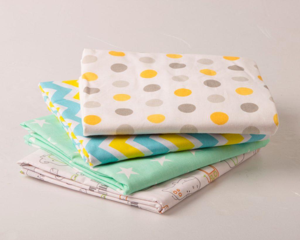 Четыре сложенные пеленки стопочкой на сером фоне