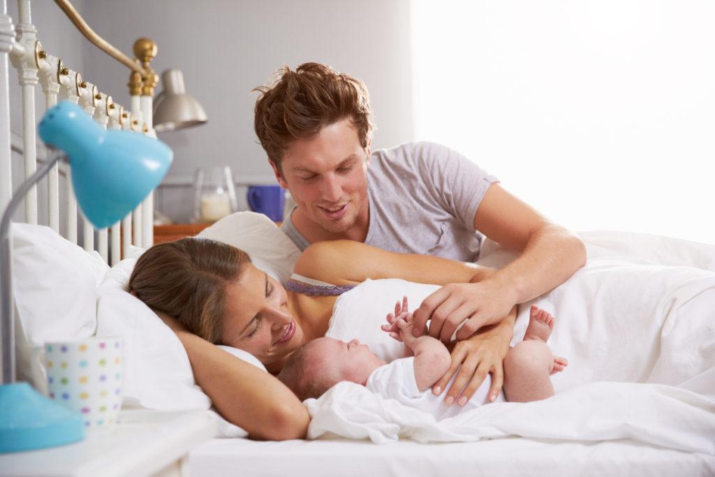 Мужчина обнимает женщину со спящим новорожденным ребенком в постели