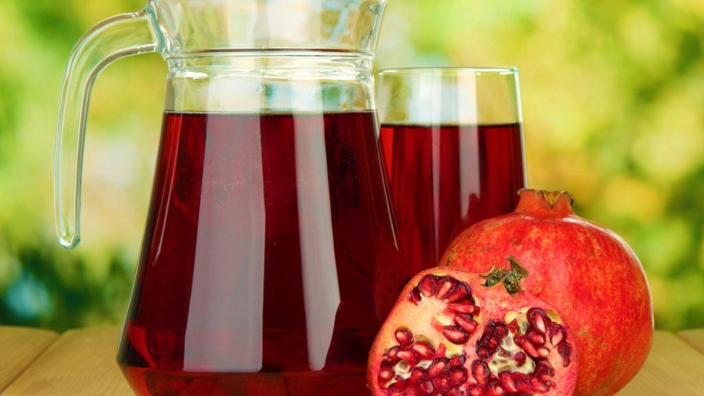 Гранатовый сок в кувшине на столе рядом с разломанным плодом граната