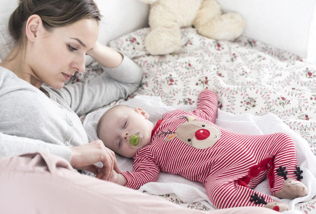 Молодая мама смотрит на спящего на кровати малыша
