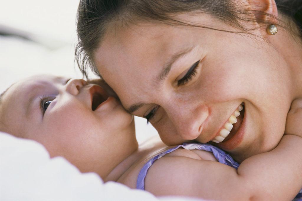 Улыбающаяся мама положила голову на грудь младенцу