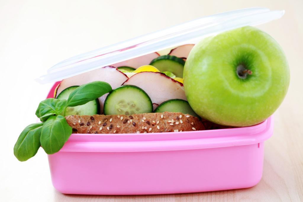 Розовый контейнер, в котором лежат яблоко, хлеб, огурец, редис, прикрытый крышкой