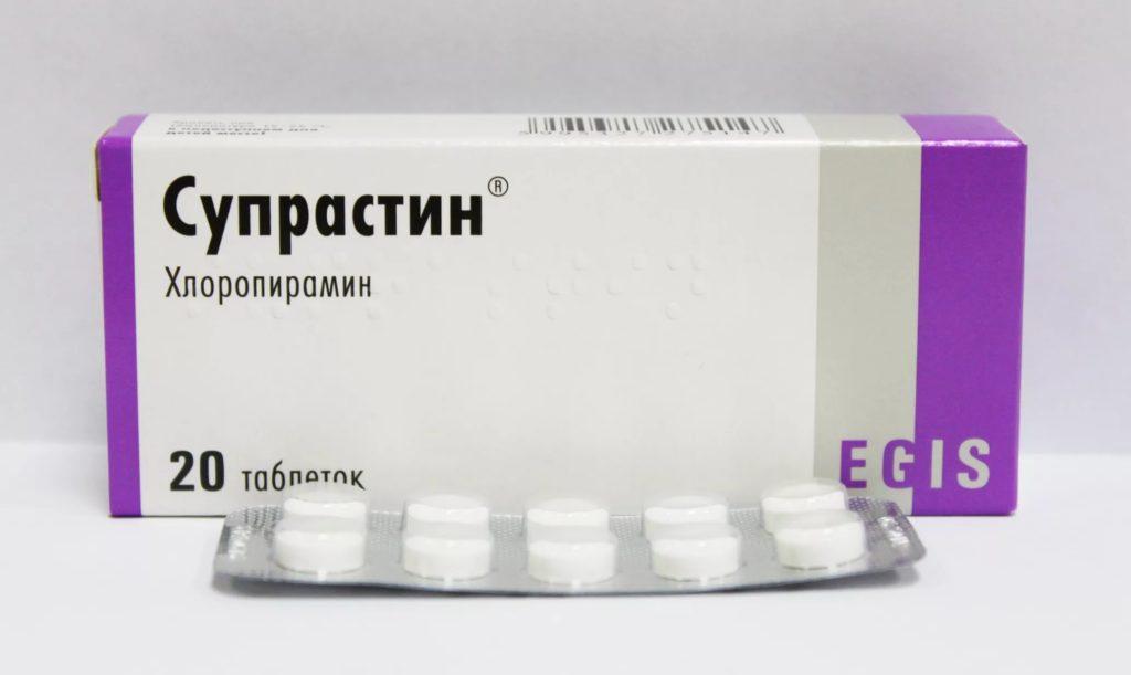 Упаковка Супрастина и блистер с таблетками на белом фоне