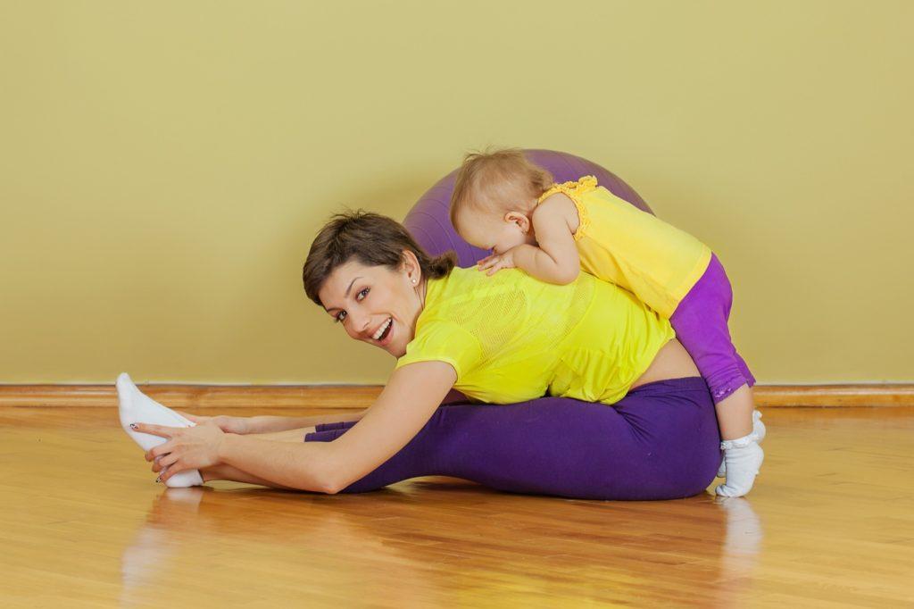 Мама занимается спортом с дочкой дома