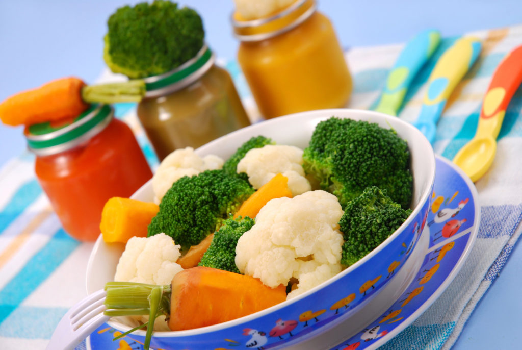 Овощи в тарелке и банки с пюре на столе