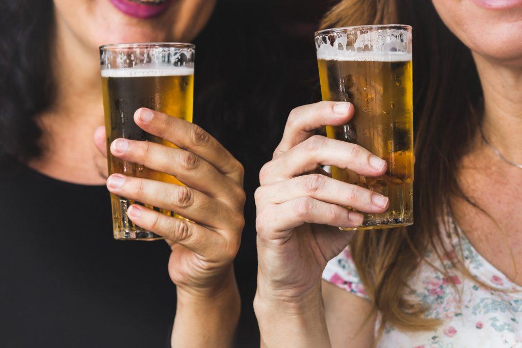 Два стакана пива в руках женщин