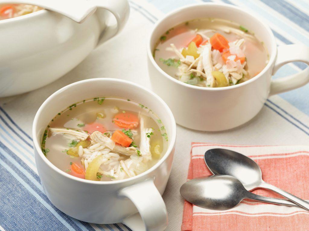Две чашки с супом и ложки на столе