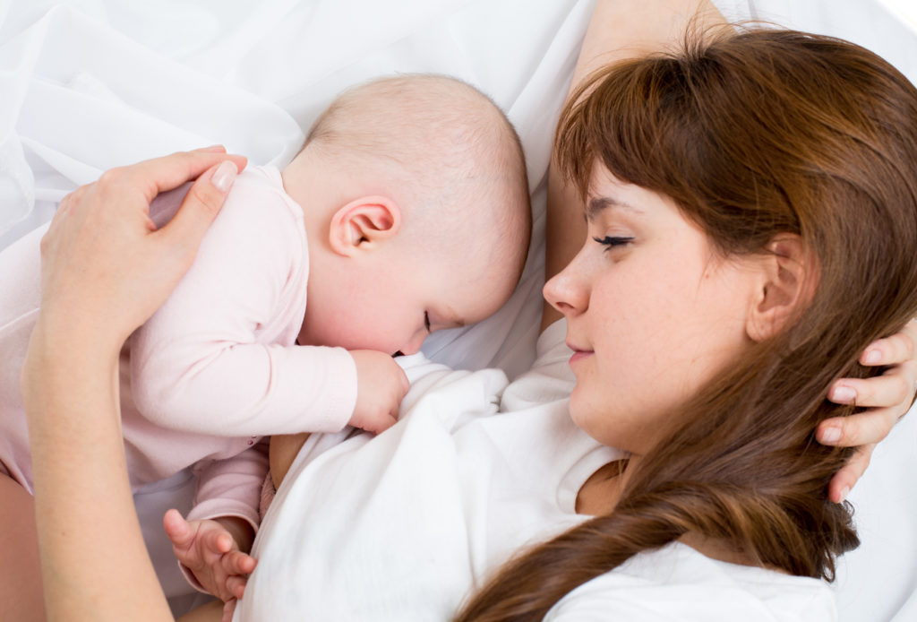 Мама кормит малыша грудью лежа