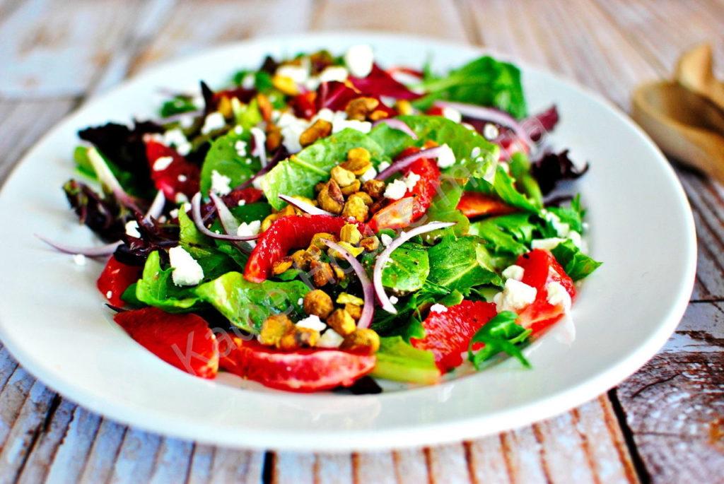 Салат овощной на белой тарелке на деревянном столе