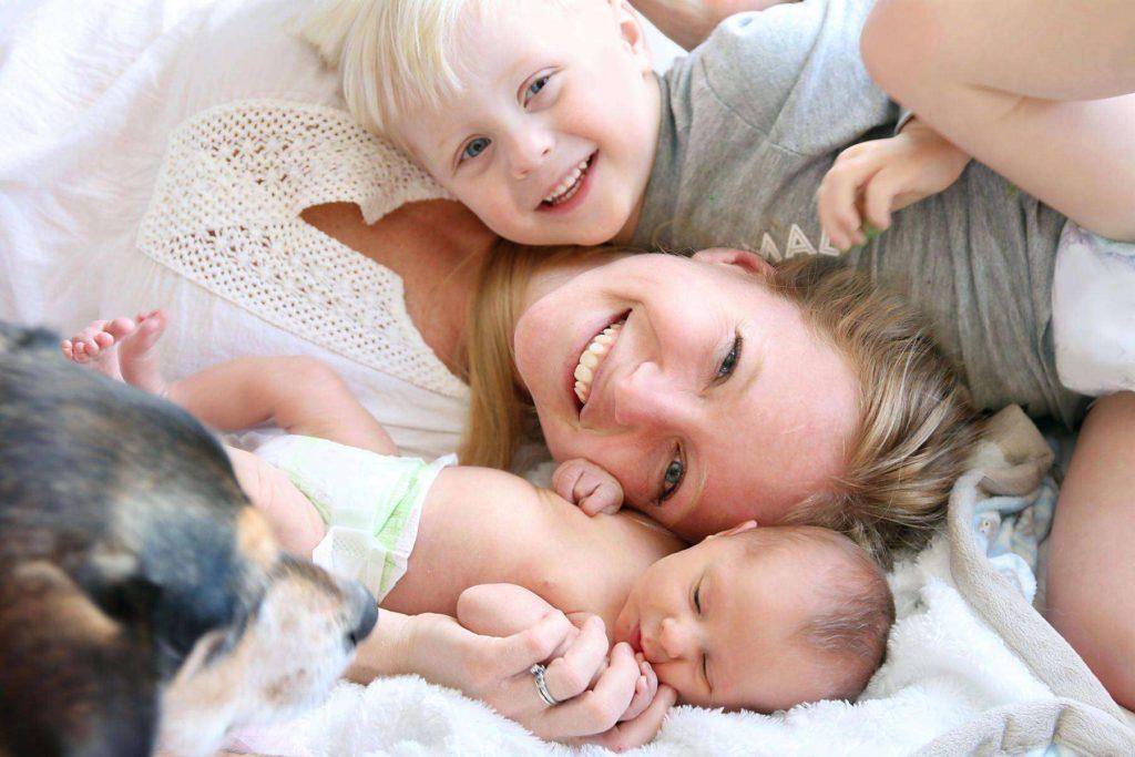 Улыбающаяся женщина лежит с двумя детьми и собакой на кровати